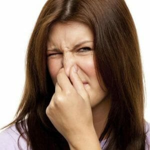 Девушка зажимает нос руками