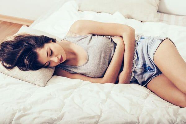 Девушка лежит и держится за живот