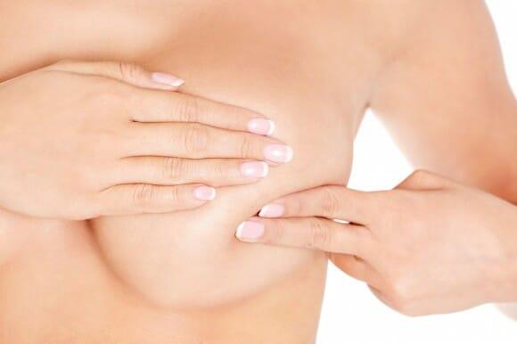 Женщина трогает грудь