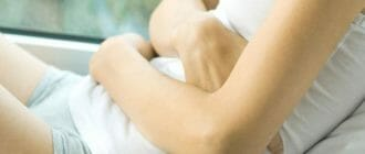 Девушка держит руки на животе