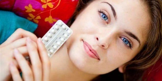 Девушка лежит с таблетками в руках