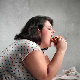 Толстая женщина ест