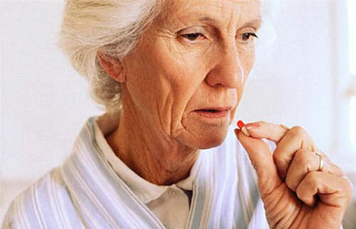 пожилая женщина пьет таблетку