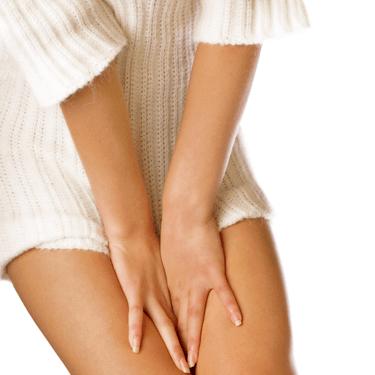 Девушка в белом свитере держит руки между ног
