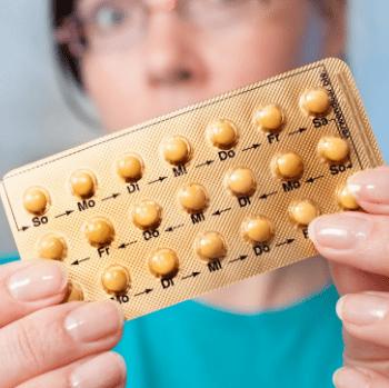 В руках гормональные таблетки